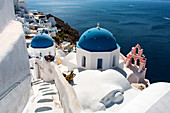 The blue domes and the pink chapel on Oia, Santorini, Greece