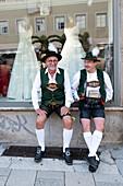 Gentlemen in Bavarian costume in front of shop window, entry of the Oktoberfest farmers to the Oktoberfest, Munich, Bavaria, Germany
