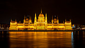 The lighted Budapest Parliament at night with the Danube in the foreground