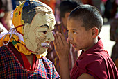 Nobize whispers with Masked Dancer at Mask Dance, Feast at Gangteng Monastery, Phobjikha Valley, Bhutan, Himalayas, Asia