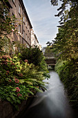 View from the waterwheel at the bird gate over Inner Stadtgraben canal, UNESCO world heritage historical water economy, Augsburg, Bavaria, Germany