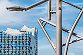 Eine moderne Straßenlampe mit der Glasfassade des Konzerthauses Elbphilharmonie, Hafencity, Hamburg, Deutschland