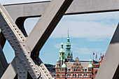 Turm des Rathauses und alte Gebäude in der Speicherstadt, eingerahmt von einer alten Brücke, Hafencity, Hamburg