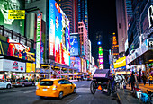 The bright lights of New York City's Times Square with an iconic yellow cab passing through, New York, United States of America, North America