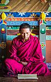 Asian monk reading on temple floor, Bhutan, Kingdom of Bhutan