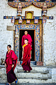 Asian monks walking out temple doorway, Bhutan, Kingdom of Bhutan