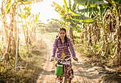 Asian woman riding bicycle on rural road, Myanmar