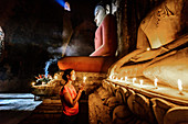 Asian woman lighting candle in temple, Myanmar