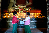 Asian girls lighting candles in Buddhist temple, Myanmar