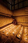 Asian monk lighting candles in temple, Myanmar