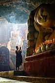 Asian monk lighting incense in temple, Myanmar