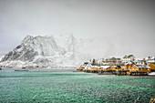 Verschneite Berge mit Blick auf die felsige Küste, Reine, Lofoten Inseln, Norwegen