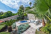 Soaking pool and armchairs on hillside patio, Coratia