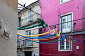 Old building facades with garlands decorated in Alfama, Lisbon, Portugal