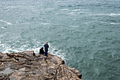 Fisherman on a cliff over the sea, Cascais, Portugal