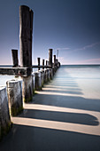 View of the wooden pillars from the old wooden footbridge on the Baltic Sea beach of Zingst, Mecklenburg-West Pomerania, Germany