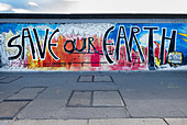 """Image with """"Save our Earth"""" text in the East Side Gallery, Friedrichshain-Kreuzberg, Berlin, Germany"""