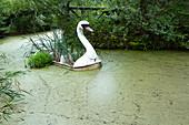 Overgrown sunken swan boat in the abandoned amusement park in the Plänterwald, Treptow, Berlin, Germany