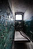 Old prison cell with original wooden platform and peeling paint on the walls, former district court prison in Berlin Köpenick, Germany