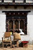 Verziertes Holzfenster, davor Stuhl und Schale mit Chili, Bhutan