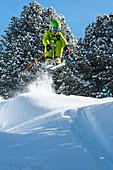 Kind springt auf Skiern im Tiefschnee, Zillertal, Tirol, Österreich
