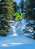Kind springt auf Ski im Tiefschnee