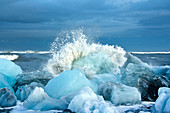 A wave breaking on the icebergs on Diamond Beach in southeast Iceland, Breidamerkursandur, Iceland, Europe