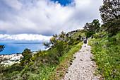 Hikers on Monte Solaro overlooking Anacapri, Capri Island, Gulf of Naples, Italy