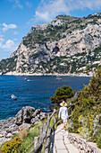 Frau auf dem Weg mit Marina Piccola im Hintergrund auf Capri, Insel Capri, Golf von Neapel, Italien
