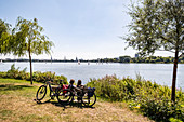 Radfahrer entspannen beim Blick über die Aussenalster in Hamburg, Norddeutschland, Deutschland