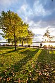 Menschen genießen den Sonnenuntergang an der Aussenalster in Hamburg, Norddeutschland, Deutschland
