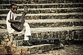 A man sits on a stone staircase and plays the guitar. Trinidat. Cuba