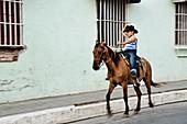 Junge mit Hut auf einem Pferd, Straßen von Trinidad, Kuba