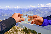 2 people toast their mountain success. Pilate. Lucerne. Switzerland. Europe
