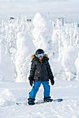 Kleiner Junge auf seinem Snowboard vor veschneiten Bäumen, Winter in Finnland