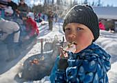 Kleiner Junge mit Marshmallowspiess im Winter, grillen in Finnland