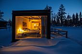 Blick in ein kleines beleuchtetes Ferienhaus im Winter, Urlaub in Finnland