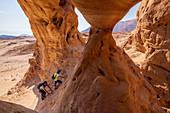 Zwei Wanderer klettern auf Felsformation in der Wüste Negev, Israel