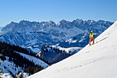 Woman on ski tour climbs to Geigelstein, Kaiser Mountains in the background, Geigelstein, Chiemgau Alps, Upper Bavaria, Bavaria, Germany
