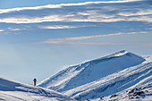 Woman on ski tour climbs to Mount Etna, volcanic crater in the background, Monte Etna UNESCO World Heritage Site, Etna, Etna, Sicily, Italy