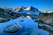 Snowy mountains are reflected in lake, Vareid, Lofoten, Nordland, Norway