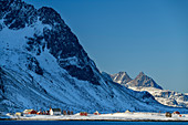 Snow-covered mountains rise above the village of Flakstad and the sea, Vareid, Lofoten, Nordland, Norway