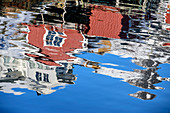 Norwegian red fishermen's houses are reflected in the sea, Klingenberg, Lofoten, Nordland, Norway