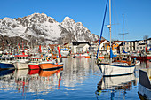 Ships in the port of Henningsvaer with snowy mountains, Henningsvaer, Lofoten, Nordland, Norway