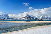 Sandy beach with snowy mountains in the background, Lofoten, Nordland, Norway
