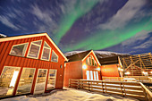 Illuminated red Norwegian houses with Northern Lights, Northern Lights, Lofoten, Nordland, Norway