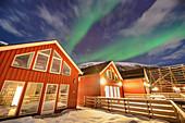 Beleuchtete rote norwegische Häuser mit Polarlicht, Nordlicht, Lofoten, Nordland, Norwegen