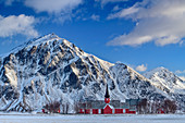 Red wooden church from Flakstad with snowy mountains in the background, Lofoten, Nordland, Norway