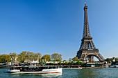 Ship travels on the Seine, Eiffel Tower in the background, UNESCO World Heritage Seine bank, Paris, France