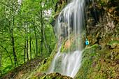 Hiker stands behind waterfall, Uracher Wasserfall, Bad Urach, Swabian Alb, Baden-Württemberg, Germany